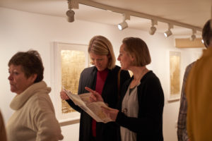 Guests at the private view of the Alchemy exhibition, looking at the guide leaflets and paintings.