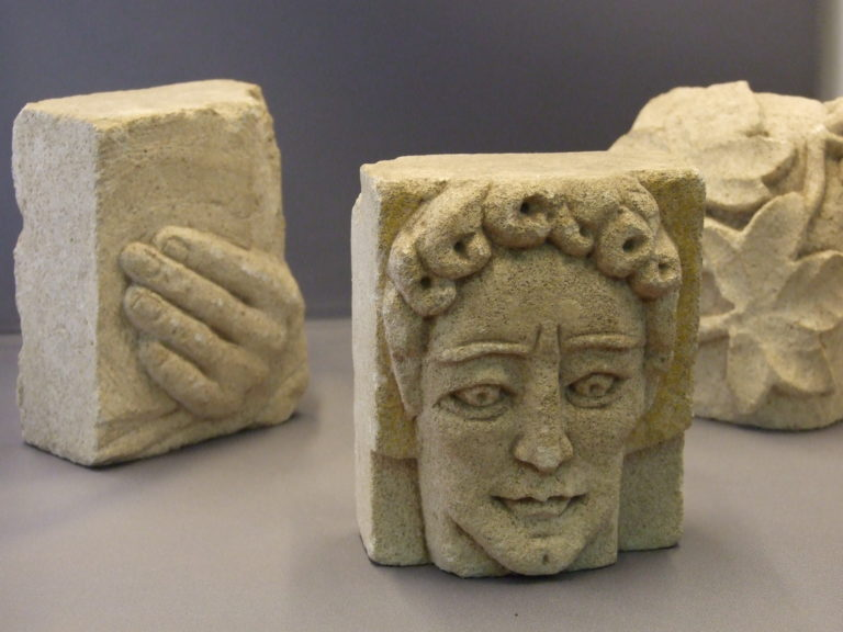 Three stone carvings by Elisabeth Muntz, a face, a hand and a leaf.