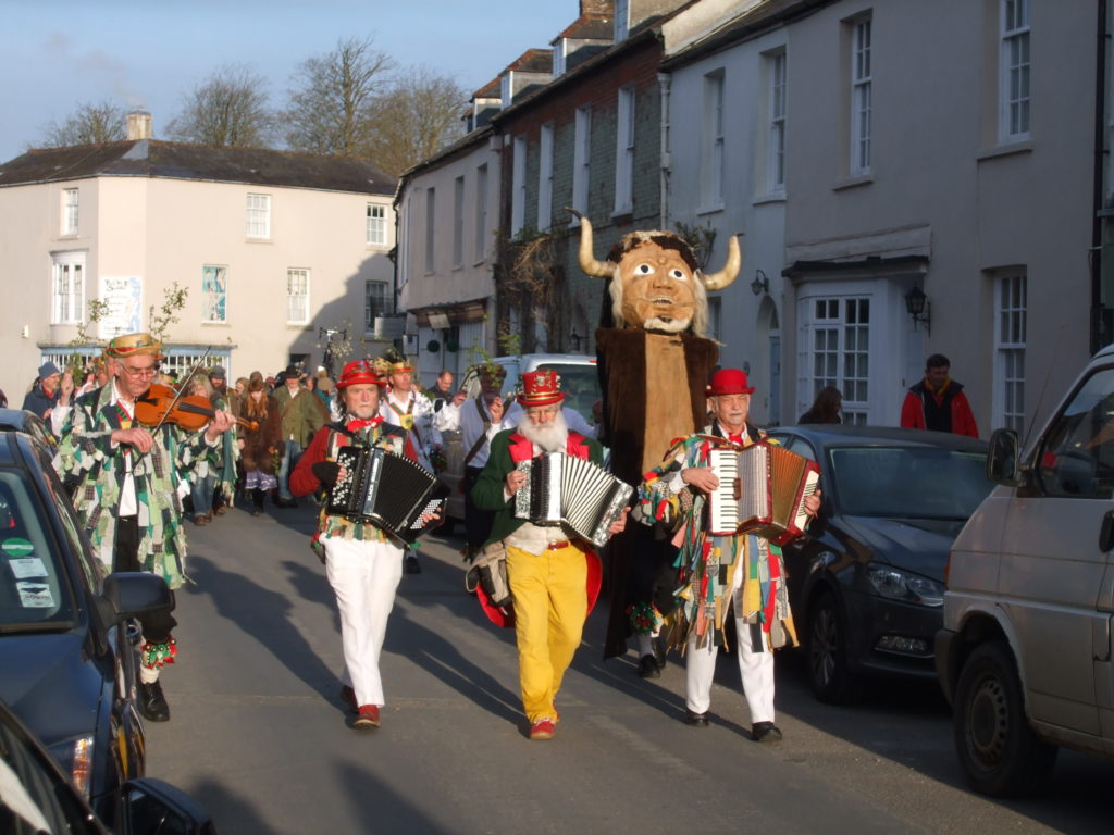 Photo of the wooden Dorset Ooser being carried through the streets by the Wessex Morris Men.