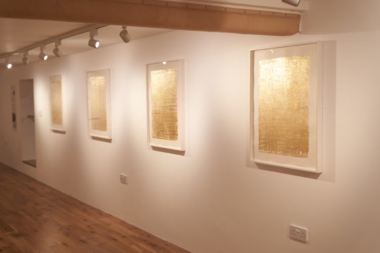 Row of gold artworks in a gallery - the Midas series.