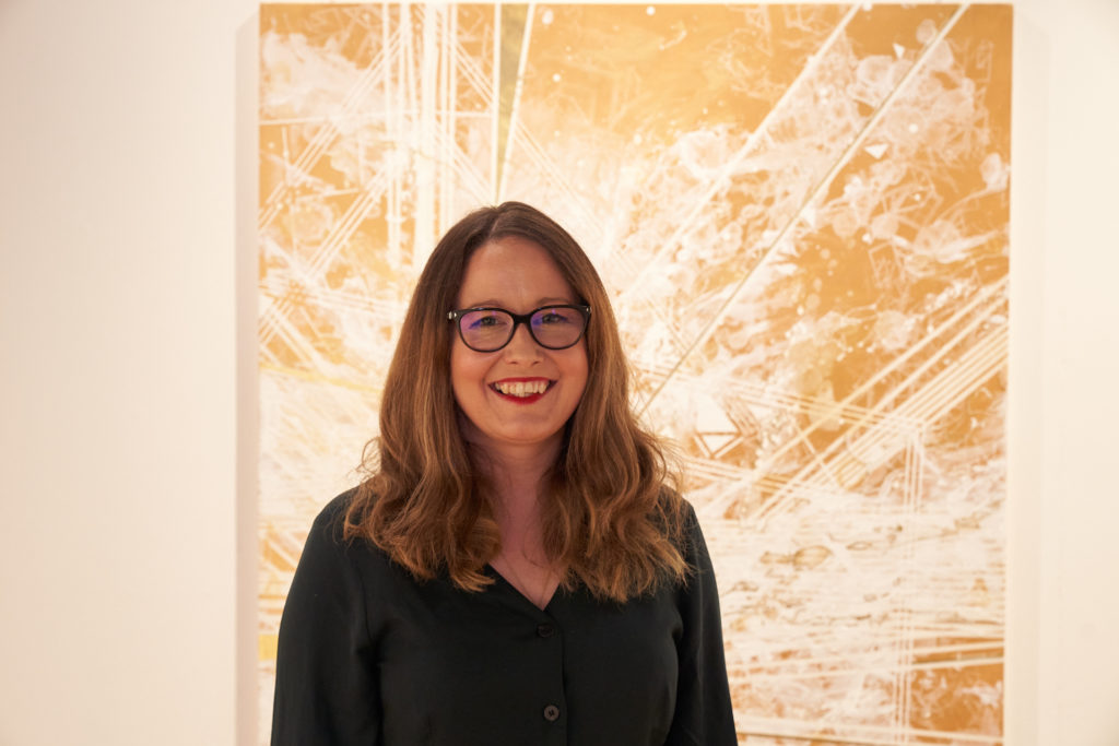 Artist Ann-Marie James standing beside her artwork, Chieftain.