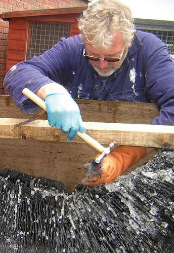 Photo of a man using a tool to remove salt crystals from the logboat.