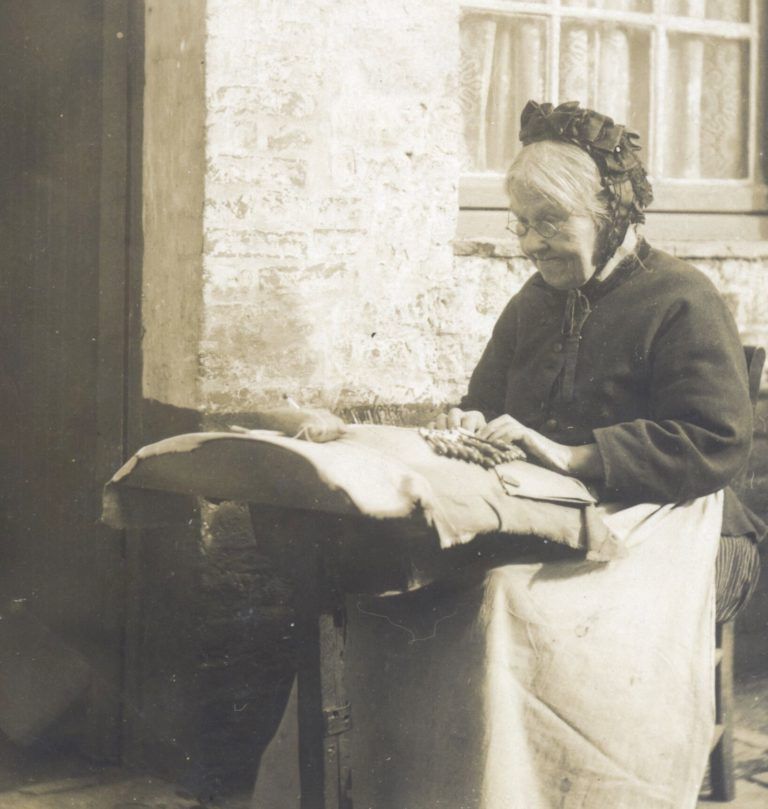 Black and white photo of an old lady making lace.