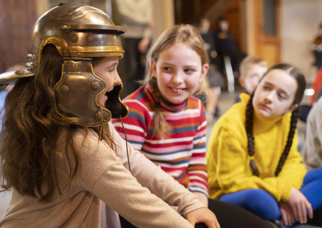 Three schoolgirls, one trying on a Roman helmet.