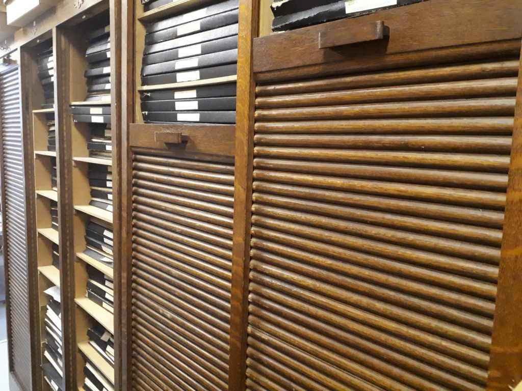 Wooden cabinets containing racks of dried plants