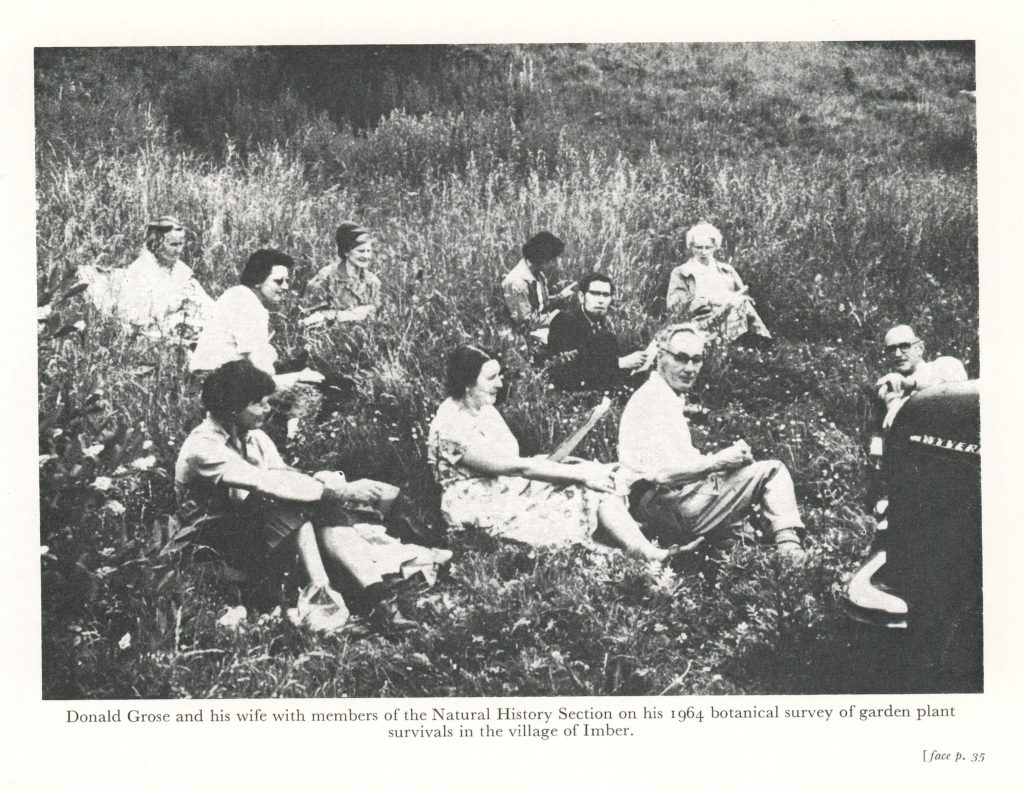 Black and white photo of Donald Grose with group of botanists sitting in grass