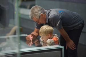 Older man looks at museum exhibit case with young boy.
