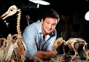 Bed Garrod surrounded by model dinosaur skeletons