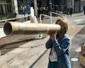 Young girl holding a cardboard tube as if it's a megaphone.