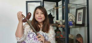 Erni Pelham holding a SE Asian artefact