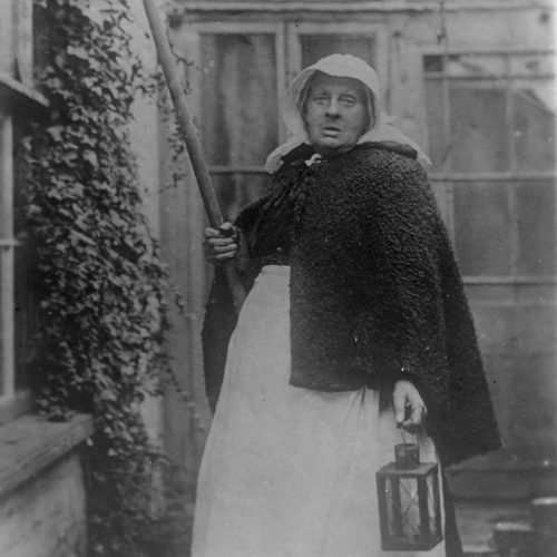 Black and white photo of Granny Cousins wearing her trademark bonnet and carrying her pole.